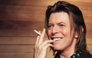An image of David Bowie smiling with a cigarette in his hand.