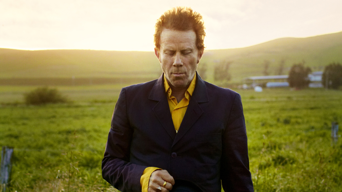 An image of musician Tom Wits walking through a field.