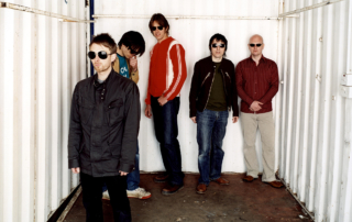 English rock band Radiohead standing in a metal crate.