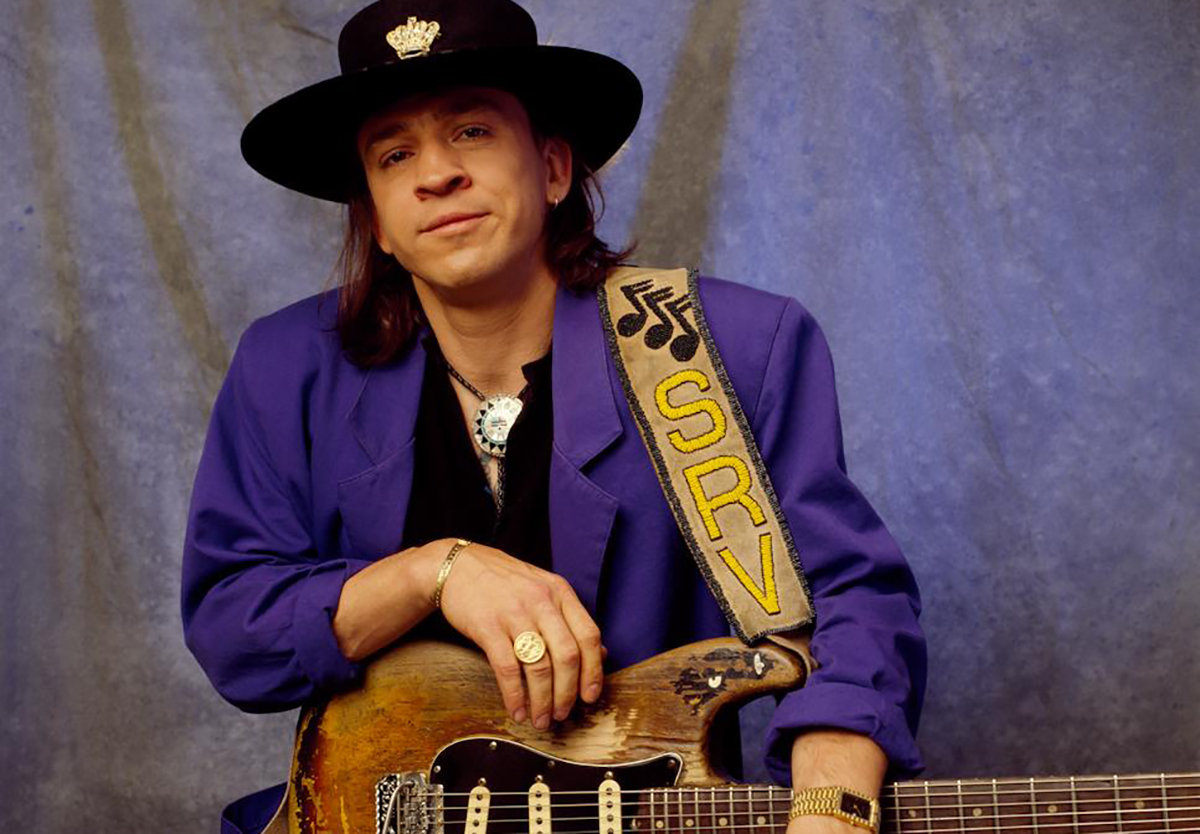 Musician Stevie Ray Vaughan standing with his signature guitar.